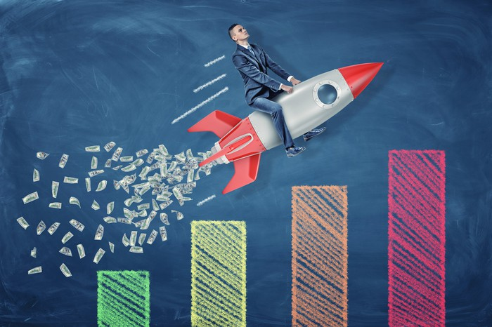 A businessman riding a rocket ship expelling cash exhaust flies over a multicolored bar chart.