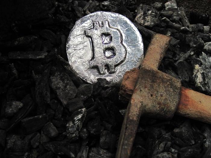 A silver coin displaying a Bitcoin symbol lies next to a pickax.
