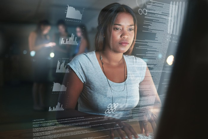 Woman writing software application code on a laptop.