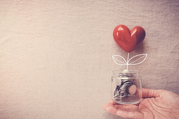 Hand holding a jar of coins with a heart growing out of them