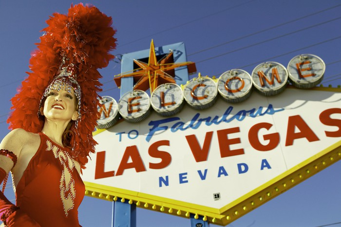 """Showgirl standing in front of """"Welcome to Las Vegas"""" sign."""