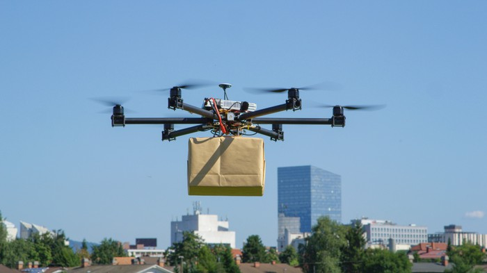 A drone carrying a cardboard box