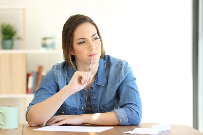 A young woman squints while touching her pencil's eraser to her chin.