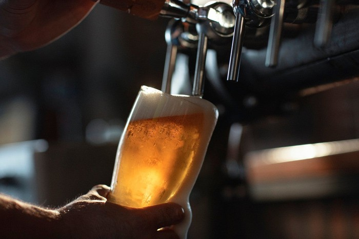 Hand holding glass with beer pouring in from a tap.