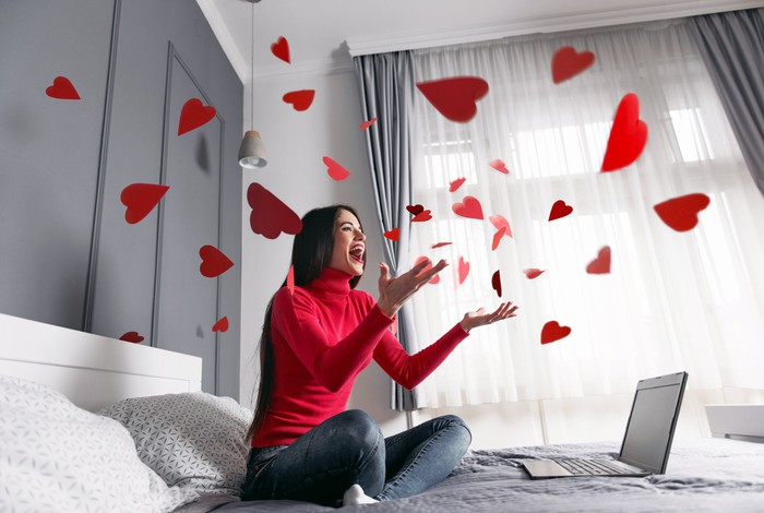 Woman sitting on bed with laptop and swirling hearts