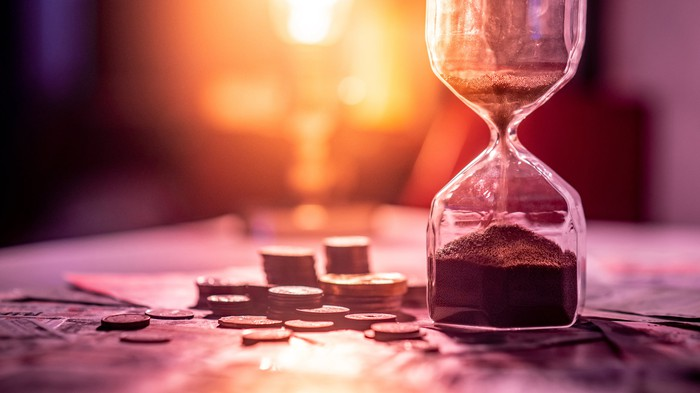 An hourglass with sands falling, sitting on a purple table with coins and bills next to it.