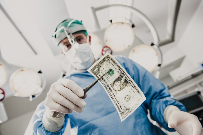 Surgeon in full gear holding a one dollar bill with a surgical instrument.