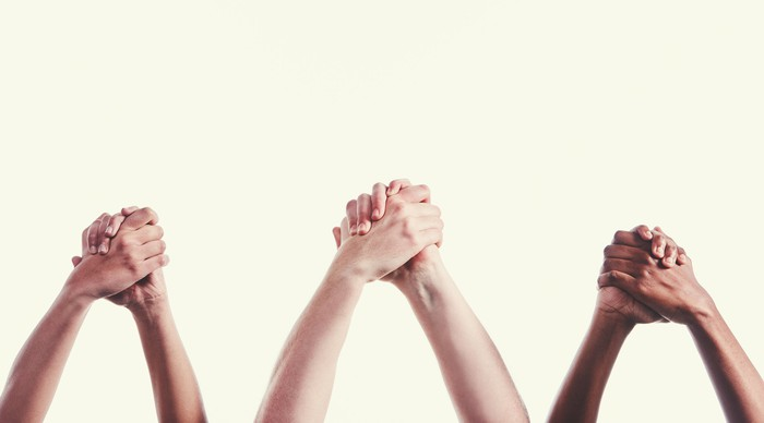 Three pairs of hands clasped together.