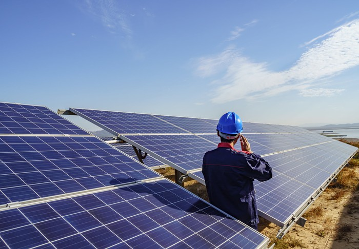 A worker leans against a solar panel while talking on his cell phone.