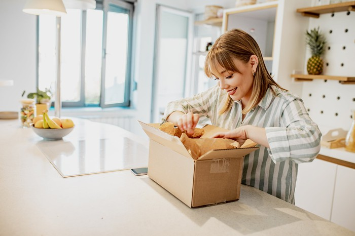 A woman opening a package in her kitchen.