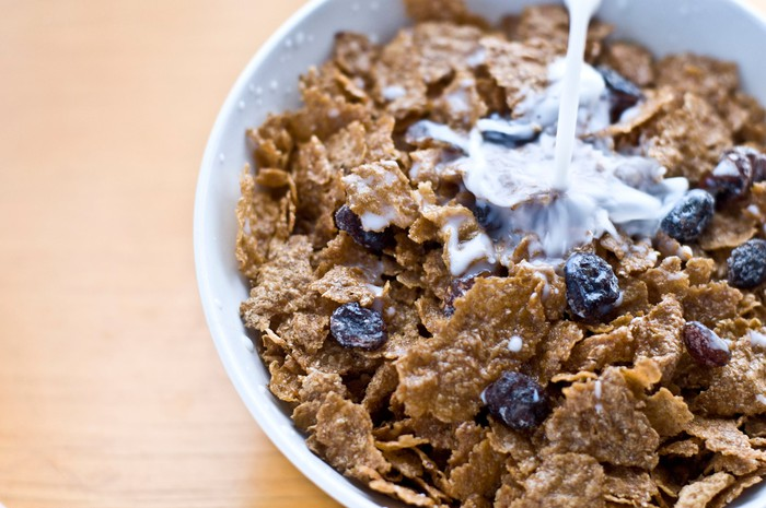 Milk being added to bowl of raisin bran cereal