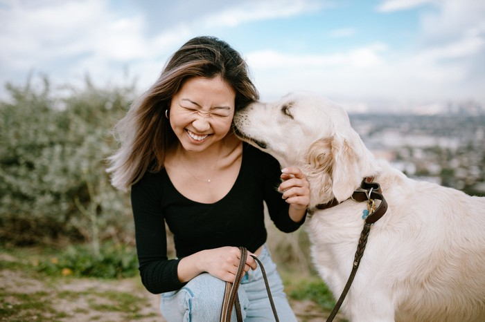 A dog kissing a girl's head outdoors