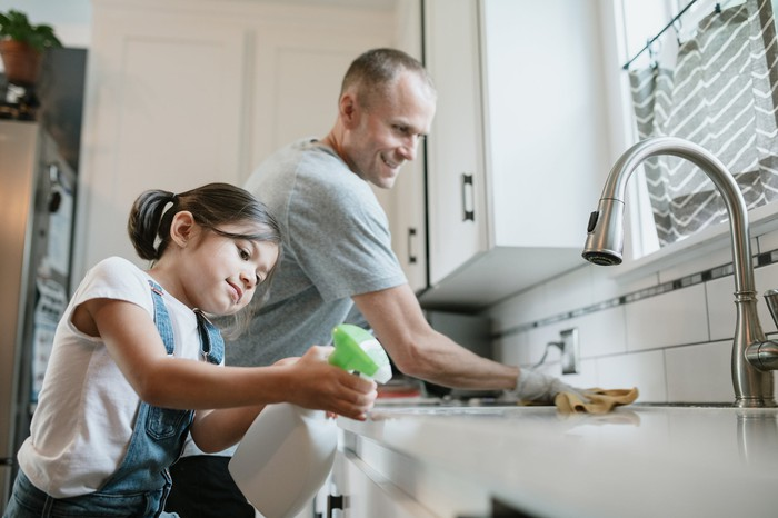 A father and his daughter clean their kitchen.