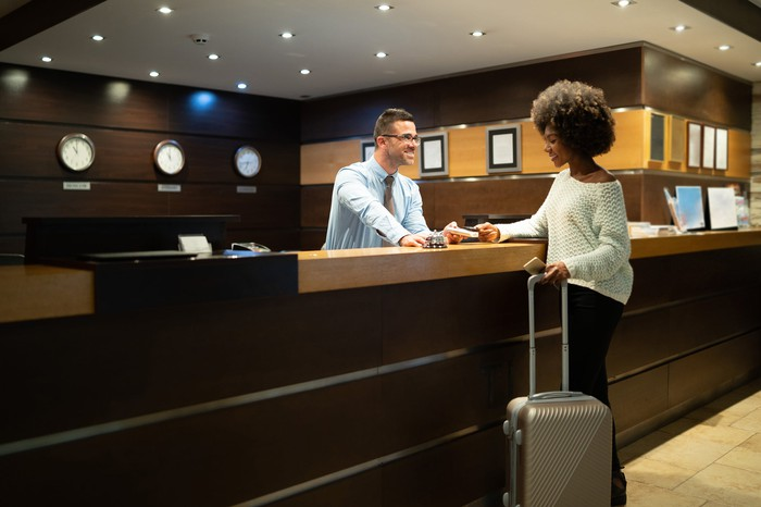 A woman checking in at a hotel.