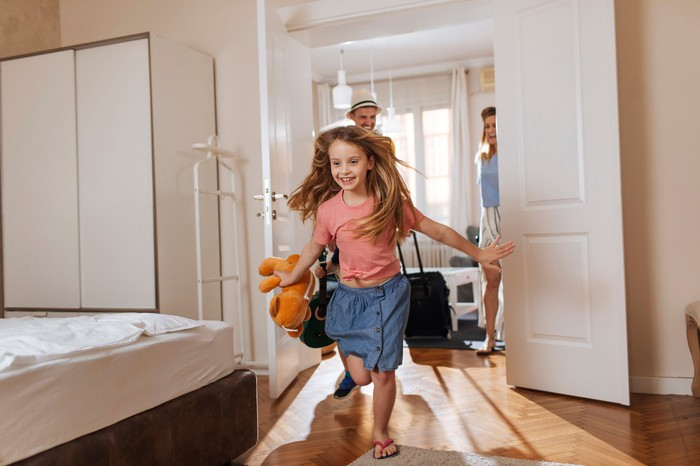 A child running and smiling into a hotel room while her mother and father are watching her in the next room.