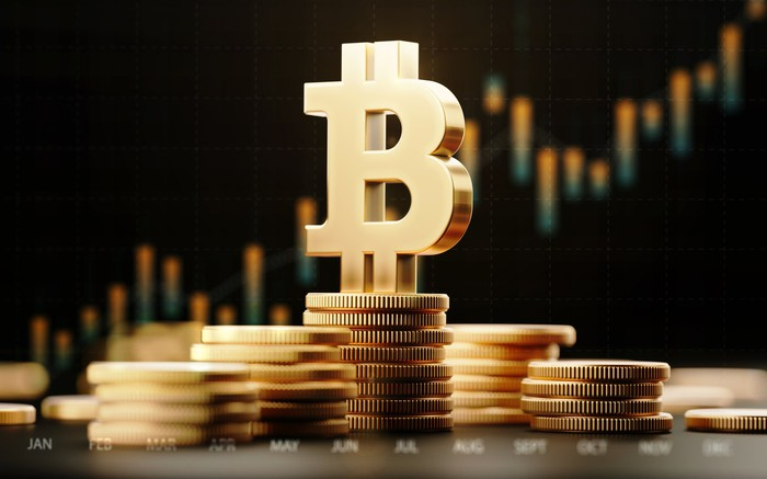 Metallic Bitcoin symbol on a stack of actual coins, with financial chart over dark background.