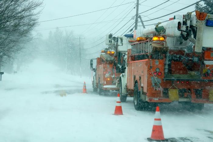 utility trucks doing repairs during winter storm