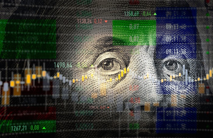 The face of Benjamin Franklin from a one hundred dollar bill with a stock chart in the background.