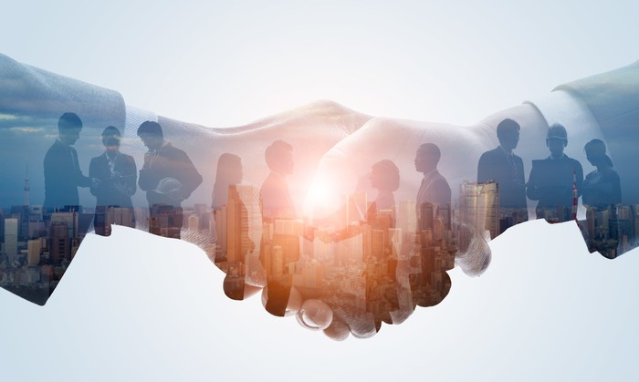 Handshake inlaid with groups of people working together