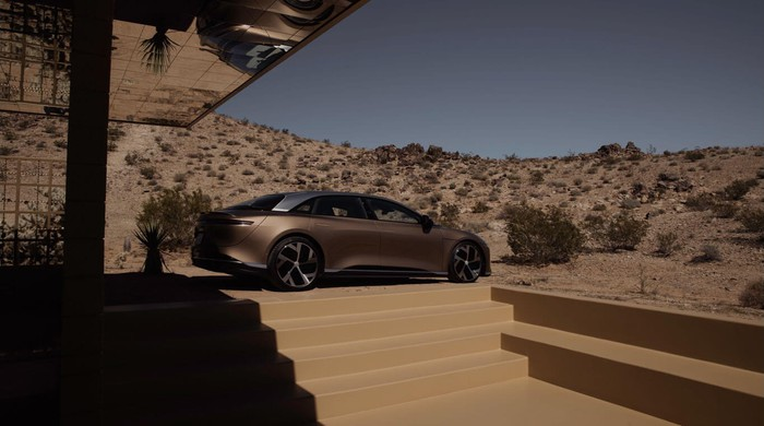 A Lucid Air parked outside of a house in the desert.