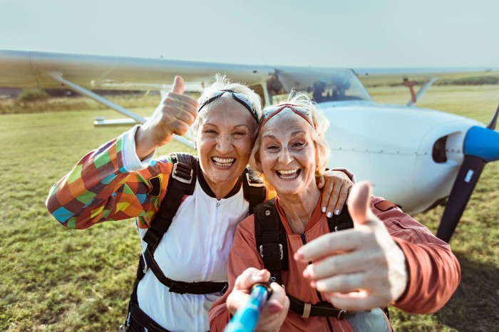 We see two happy senior women with thumbs up next to a propeller plane.