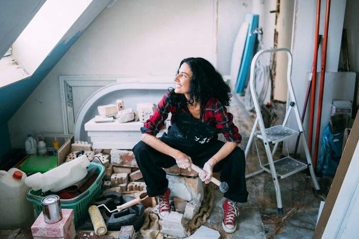 A woman sitting in a room that she is remodeling.