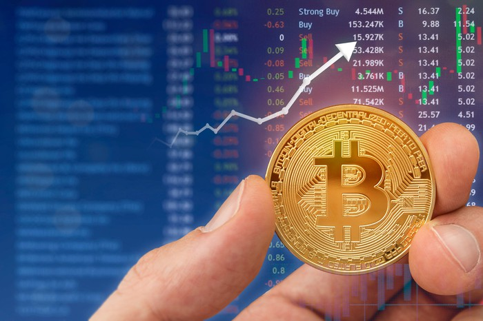 A hand holds a golden coin displaying the Bitcoin symbol with a rising chart in the background.