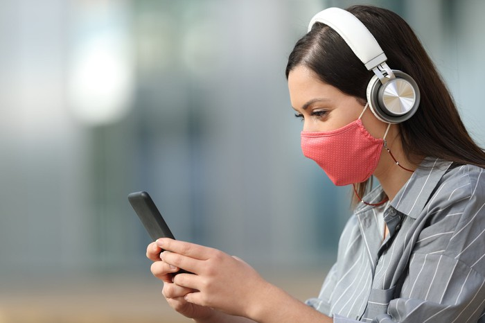 A woman wearing a red face mask and white headphones uses her smartphone.