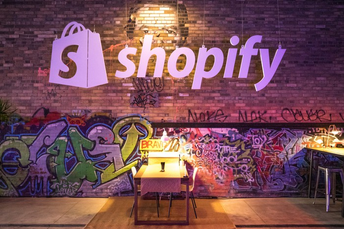 The Shopify logo above a cafeteria table and a brick wall decorated with graffiti.