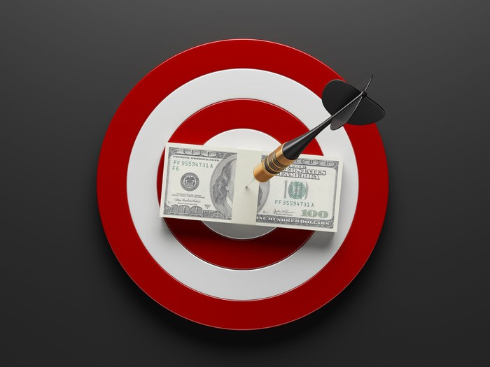 Red and white dart board, with an arrow going through a stack of hundred dollar bills in the bull's eye.