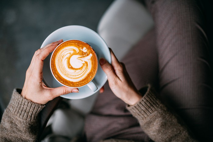 Overhead view of a person's hands holding a mug of latte