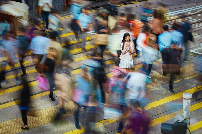 A young woman uses her smartphone in the middle of a crowded crosswalk.