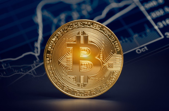 A physical gold Bitcoin stood on its side in front of a digital chart with volume data.