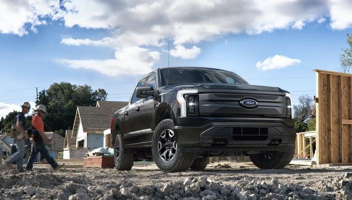 Une Ford F-150 Lightning Pro noire, une camionnette électrique conçue pour les véhicules commerciaux, présentée sur un chantier de construction.