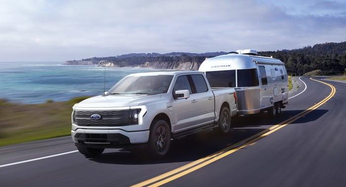 Un Ford F-150 Lightning Lariat argent 2022, une camionnette électrique, remorqué une remorque de camping sur une route côtière.