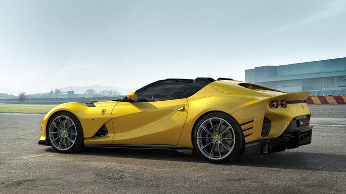 A yellow Ferrari 812 Competizione A, a two-seat V-12-powered open-topped exotic sports car.