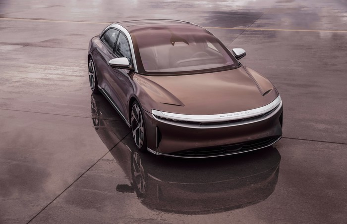 A brown Lucid Air, a sleek electric luxury sports sedan displayed on a parking lot.