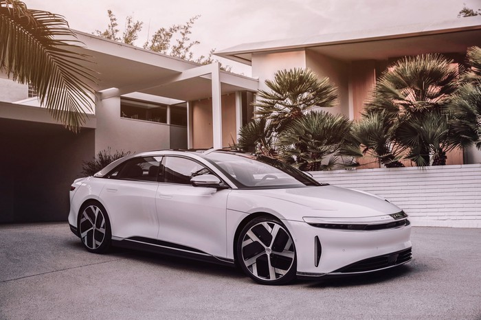 A white Lucid Air, a sleek electric luxury sedan, in the driveway of a stylish house.
