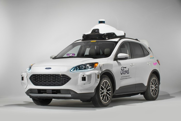 A white Ford Escape Hybrid SUV with visible self-driving sensor hardware and Ford, Lyft, and Argo AI logos.