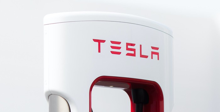 A close-up of the Tesla logo on a Supercharger charging unit.