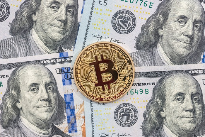 A physical Bitcoin laid atop a pile of one hundred dollar bills.