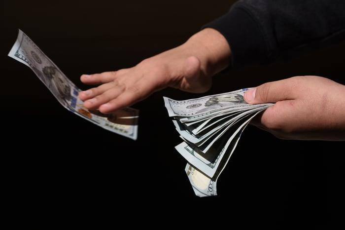 Hands holding hundred dollar bills