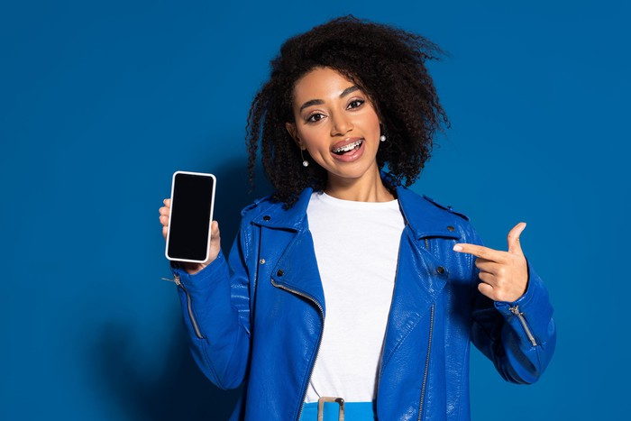 A young woman points at her smartphone.