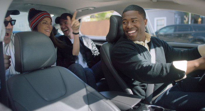 Smiling Uber driver with passengers