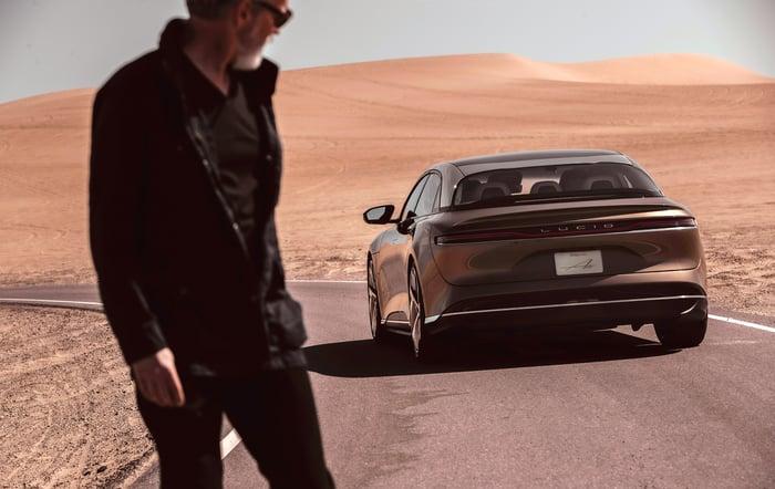 man looking at Lucid Air luxury electric sedan driving by
