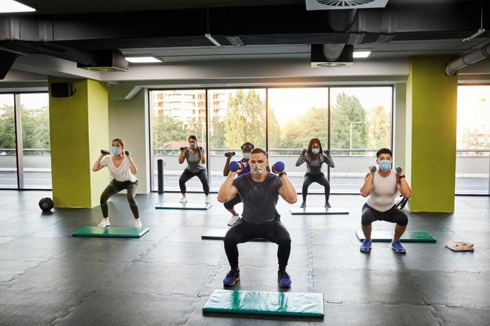 indoor fitness class doing squats