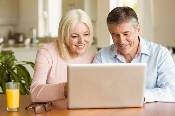 Older man and woman at laptop, smiling