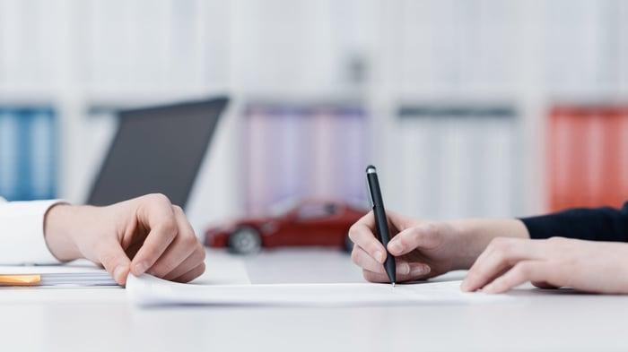 Hands signing paperwork.