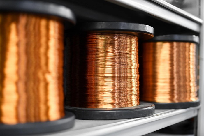 Three spools of copper wire on a shelf.