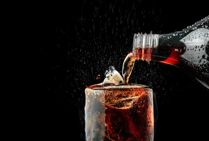 A dark soft drink is poured into a glass against a dark background.